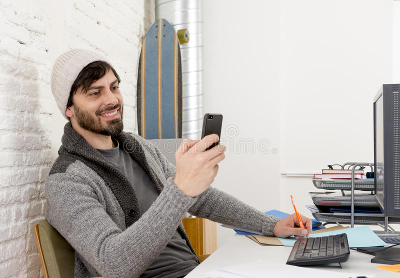 Attractive man in hipster beanie and trendy style businessman working happy at home office with desktop computer. Young attractive man in hipster beanie and royalty free stock photos