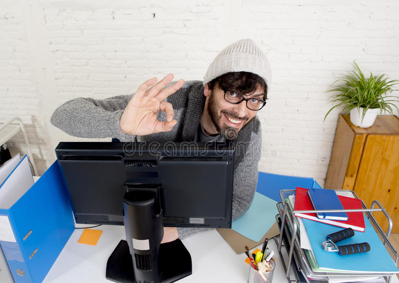Attractive man hipster trendy style businessman working home office with desktop computer. Young attractive man in hipster beanie and trendy style businessman royalty free stock image