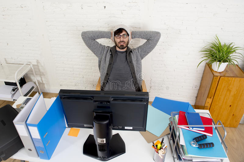 Attractive man hipster trendy style businessman working home office with desktop computer. Young attractive man in hipster beanie and trendy style businessman royalty free stock photo
