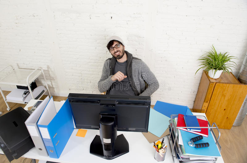 Attractive man hipster trendy style businessman working home office with desktop computer. Young attractive man in hipster beanie and trendy style businessman royalty free stock images