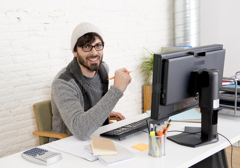 Attractive man hipster trendy style businessman working home office with desktop computer. Young attractive man in hipster beanie and trendy style businessman stock photography