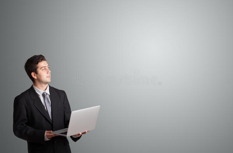 Attractive man holding a laptop and presenting copy space. Attractive young man holding a laptop and presenting copy space stock photography