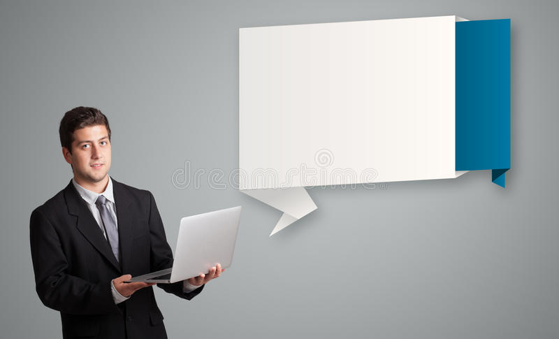 Attractive man holding a laptop and presenting modern origami co. Attractive young man holding a laptop and presenting modern origami copy space royalty free stock image