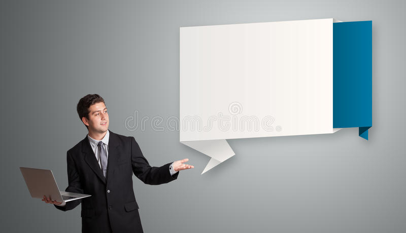 Attractive man holding a laptop. Attractive young man holding a laptop and presenting modern origami copy space stock photos