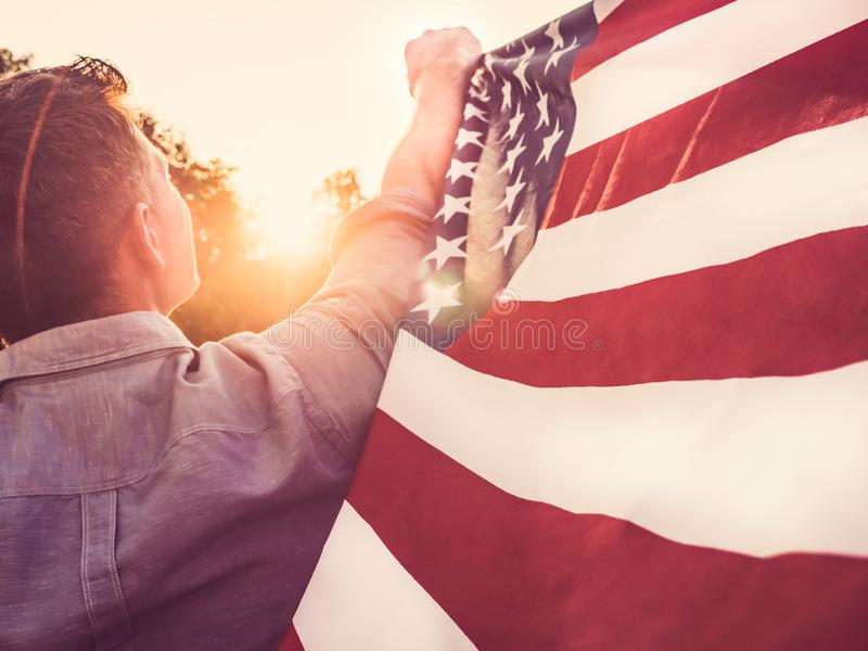 Attractive man holding waving in the wind US flag. Against the backdrop of the rays of the setting sun. View from the back, closeup. Preparing for the holidays royalty free stock images