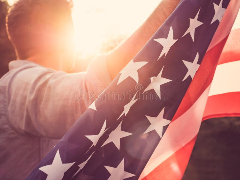 Attractive man holding waving in the wind US flag. Against the backdrop of the rays of the setting sun. View from the back, closeup. Preparing for the holidays stock image