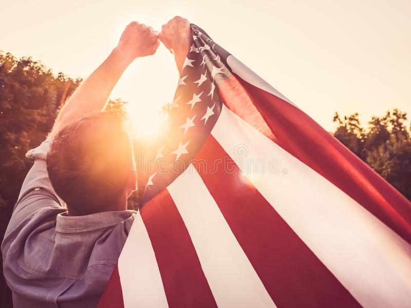 Attractive man holding waving in the wind US flag. Against the backdrop of the rays of the setting sun. View from the back, closeup. Preparing for the holidays royalty free stock photos