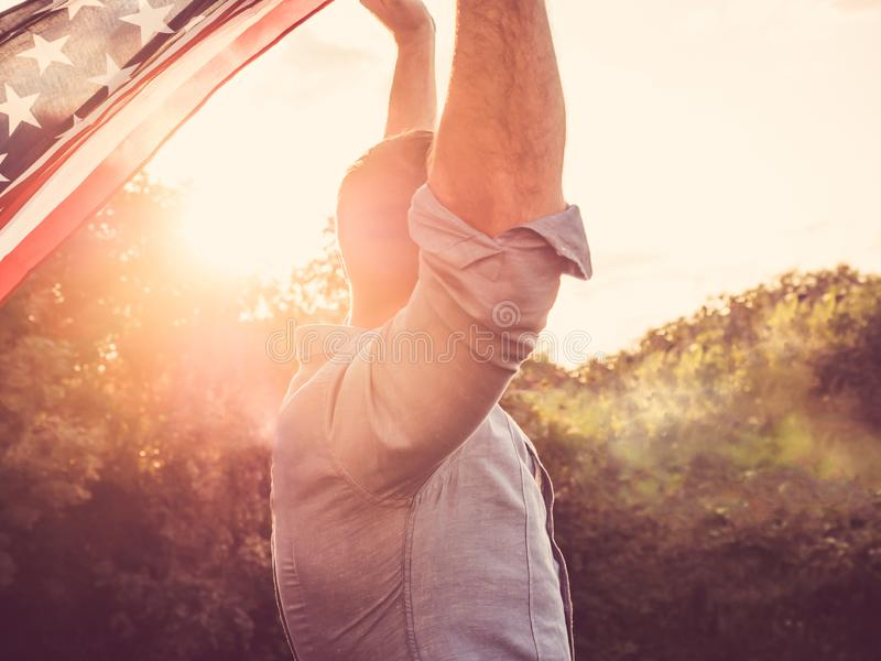 Attractive man holding waving in the wind US flag. Against the backdrop of the rays of the setting sun. View from the back, closeup. Preparing for the holidays royalty free stock image
