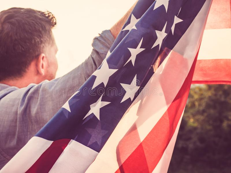 Attractive man holding waving in the wind US flag. Against the backdrop of the rays of the setting sun. View from the back, closeup. Preparing for the holidays stock images