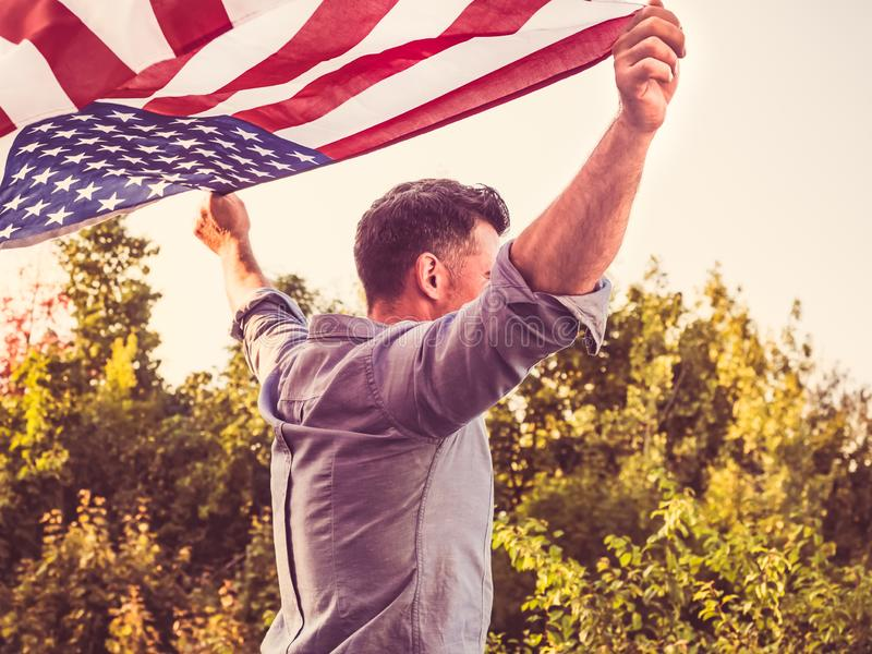 Attractive man holding waving in the wind US flag. Against the backdrop of the rays of the setting sun. View from the back, closeup. Preparing for the holidays stock photos