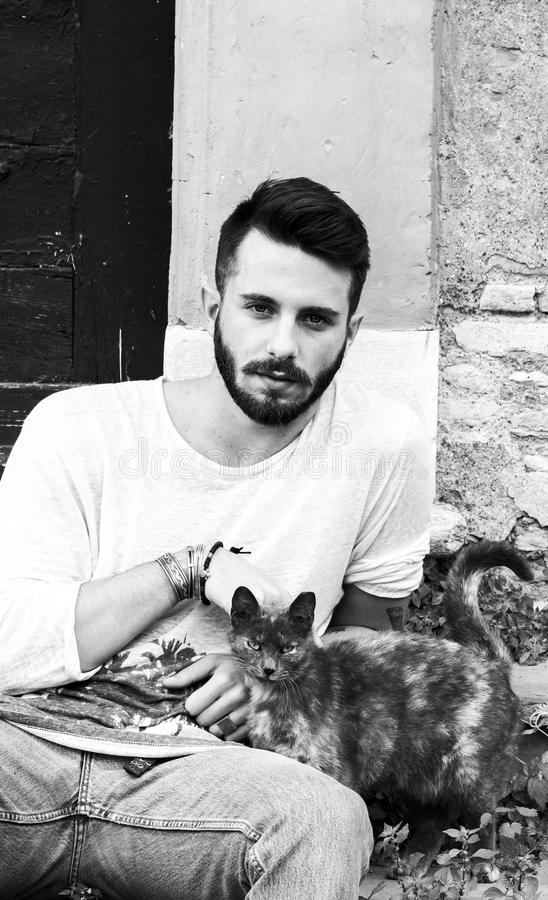 Attractive man. Model sitting in a courtyard with dappled cat - attractive man with seductive look stock photo
