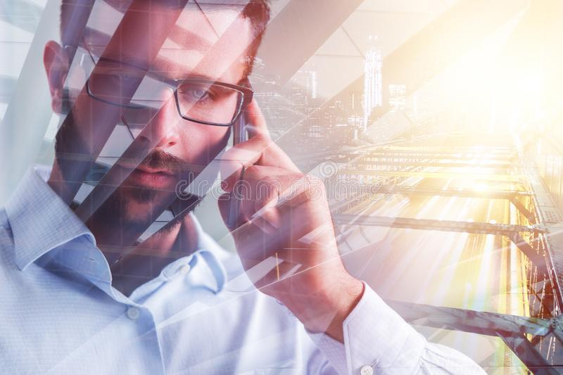Attractive man on the phone. Portrait of attractive european businessman talking on the phone on abstract city background. Double exposure stock photo