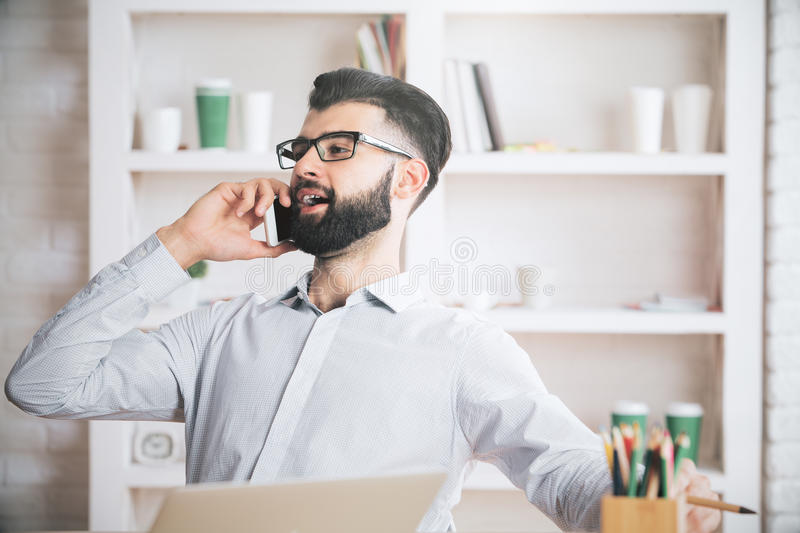 Attractive man on phone. Attractive young man sitting at his office desk with laptop, supplies, other items and talking on mobile phone. Communication concept royalty free stock photography