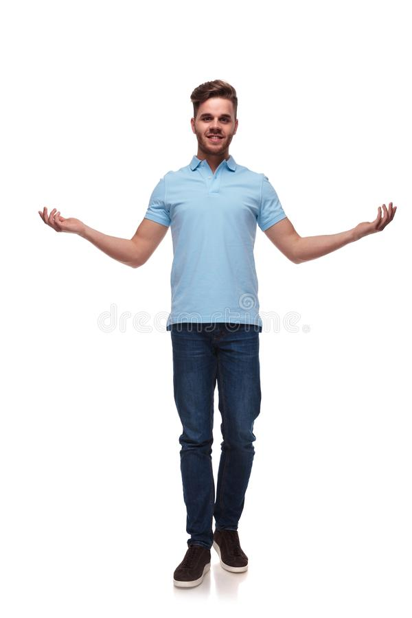 Attractive man in polo shirt making a welcoming gesture. With hands while stepping forward on white background, full length picture royalty free stock photography