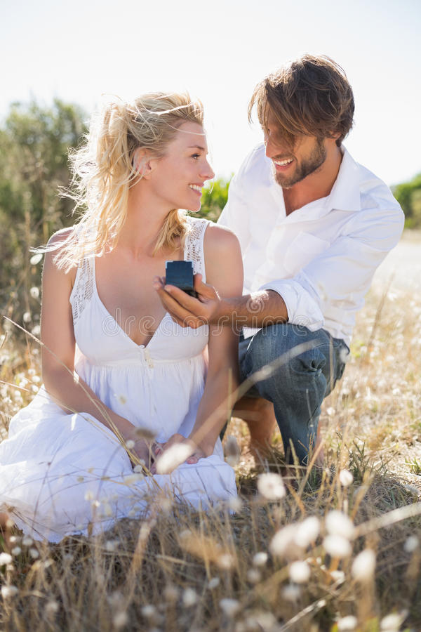 Attractive man proposing to his girlfriend in the country. Attractive men proposing to his girlfriend in the country on a sunny day stock photos