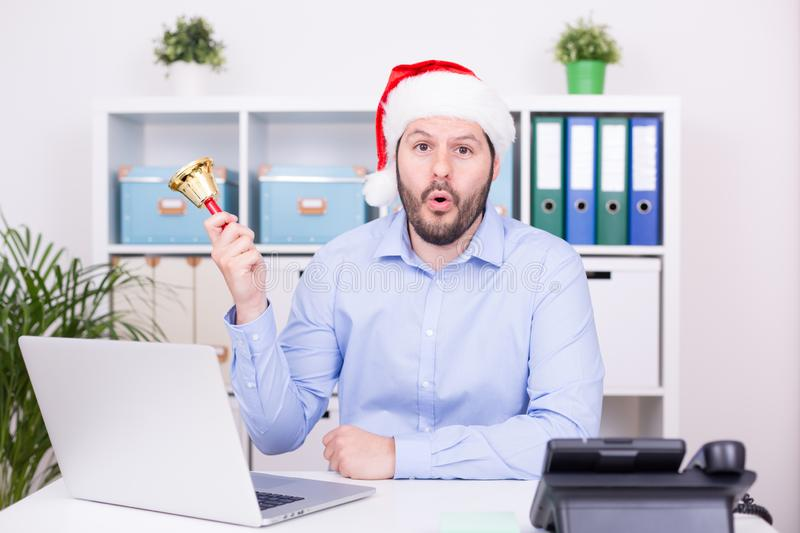 Attractive man is ringing the bell at christmas time. Business, christmas and new year celebration concept stock photography