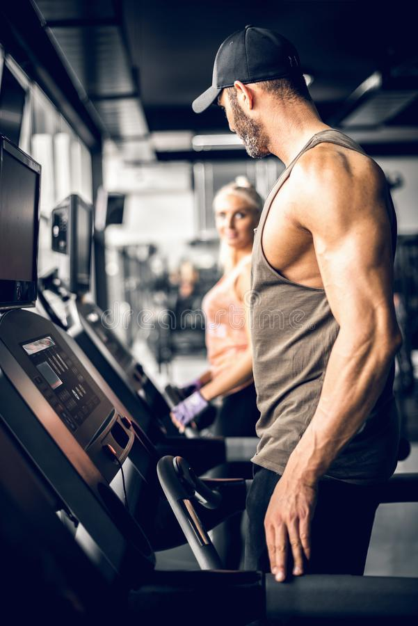 Attractive man running on treadmill and looking at girl royalty free stock photos