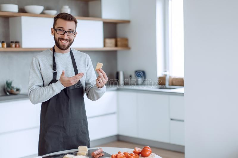 Attractive man showing a piece of delicious cheese stock images