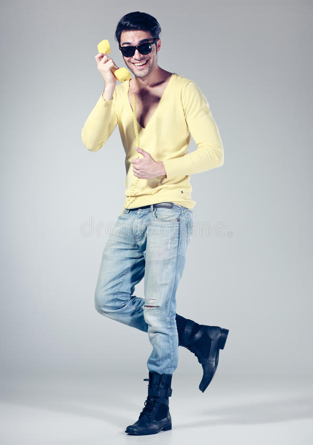 Download Attractive Man Smiling Talking On A Yellow Phone Stock Photos - Image: 26607223