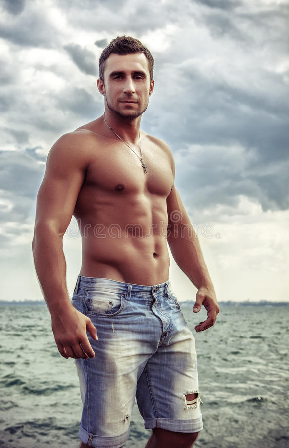 Attractive man staying in the sea. Young attractive man staying in the sea royalty free stock photography