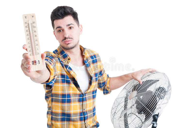 Attractive man with thermometer use electric fan to cool down. During summertime isolated on white stock images
