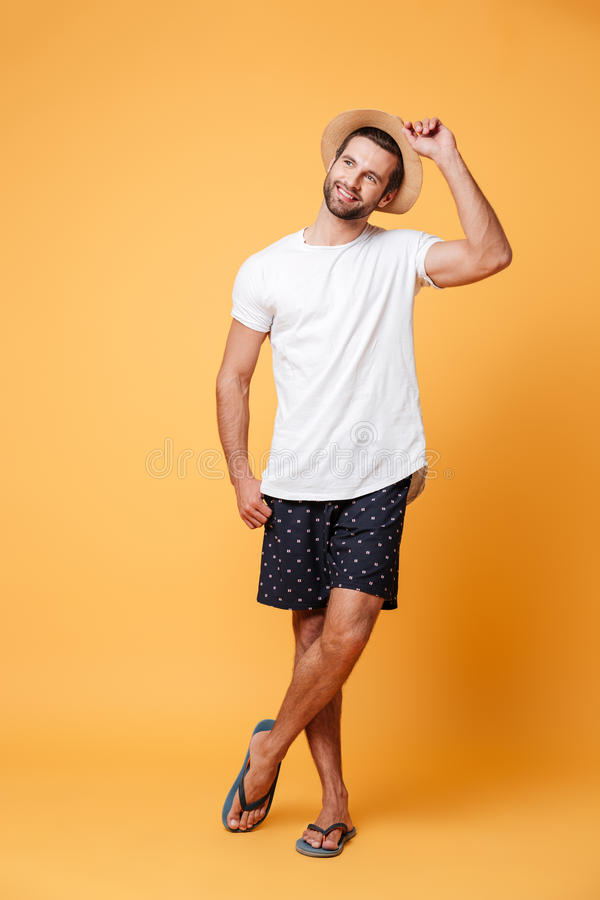 Attractive man wearing flip flops and hat looking away isolated. Over orange royalty free stock images