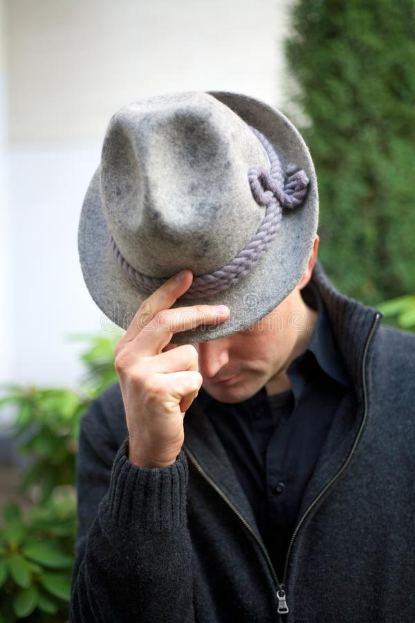 Man with Hat - Bowing before the Audience. Thank you! Bowing before the audience - Attractive man wearing hat holding two fingers spread on it stock photography