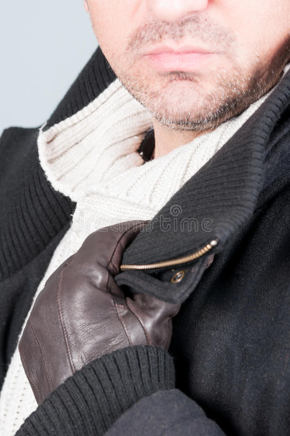 Attractive man wearing soft knitted pullover and black jacket. With leather gloves as modern winter clothes stock photo