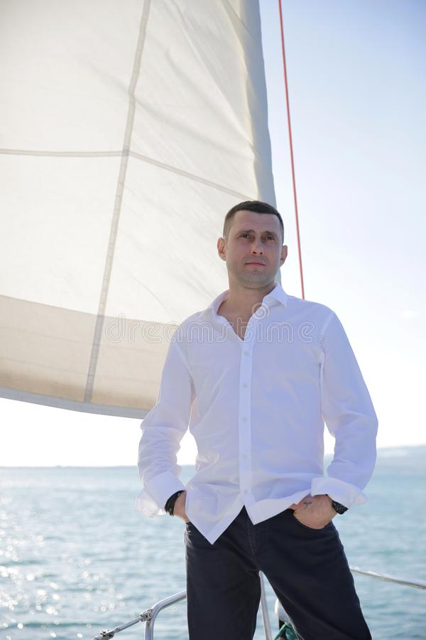 Attractive man in a white shirt stands at the sail of a yacht at sea. Sailing, tourism, travel and people concept. royalty free stock photo