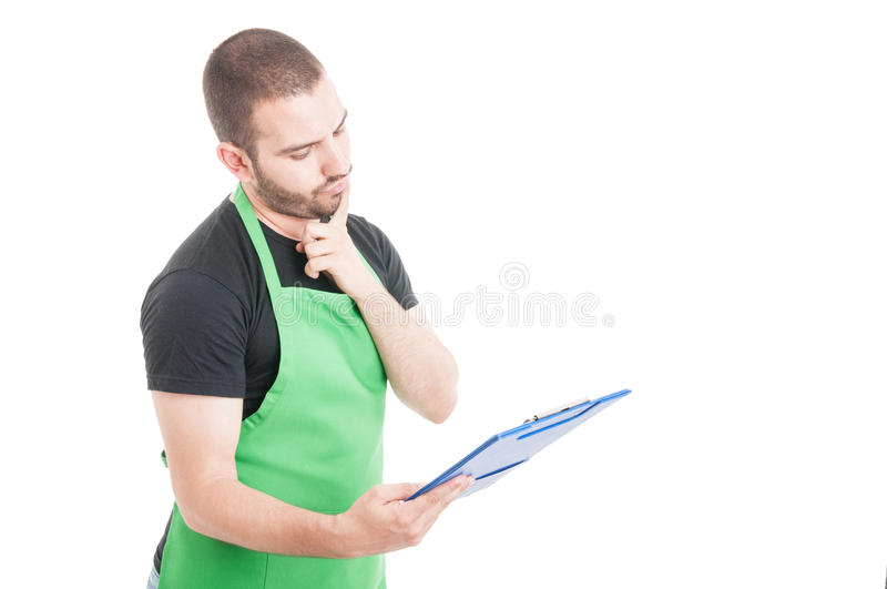 Attractive market seller being pensive holding clipboard. Isolated on white background with copy space area royalty free stock image