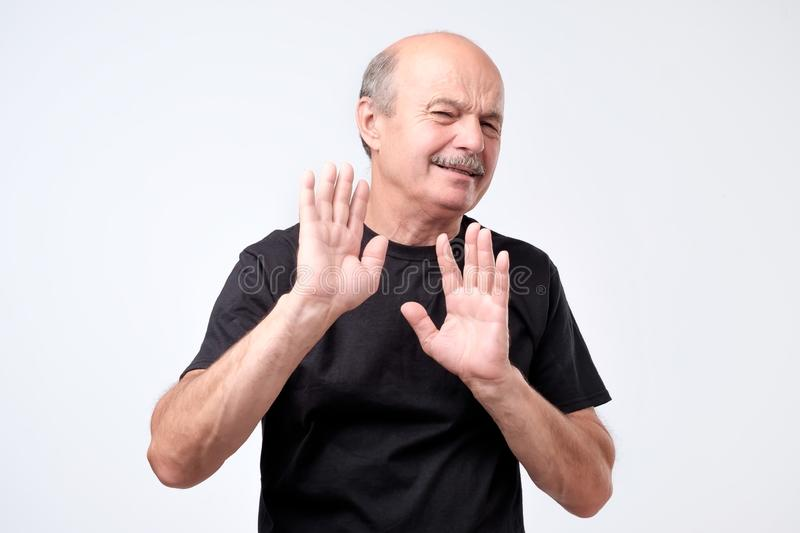 Attractive mature bald man showing refusal gesture. Attractive mature man showing refusal gesture. It is not for me, leave me in piece, has angry expression stock photos