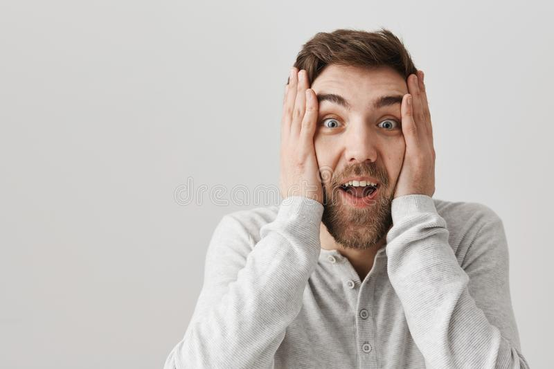 Attractive mature bearded guy holding hands on face, being shocked or amazed, smiling and staring at camera over gray. Background. Man can not believe that he royalty free stock images