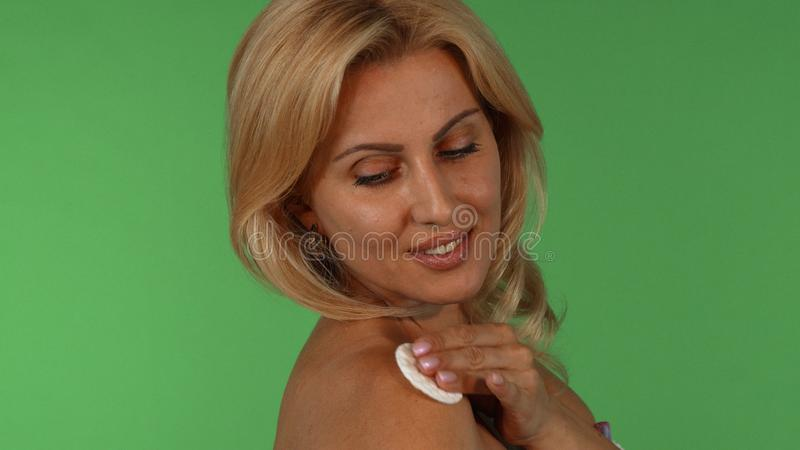 Stunning mature woman smiling to the camera while using cotton pad on her skin royalty free stock photo