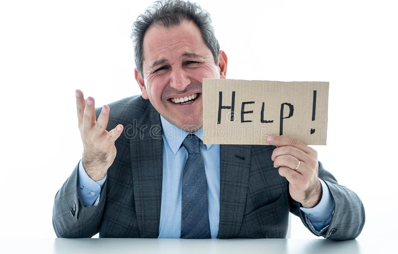 Attractive mature businessman overwhelmed and tired holding a help sign stock photography