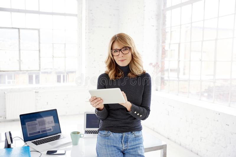 Attractive mature businesswoman using digital tablet while working in the office stock photography