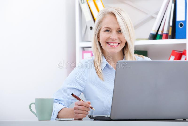 Attractive mature businesswoman working on laptop in her workplace stock photography