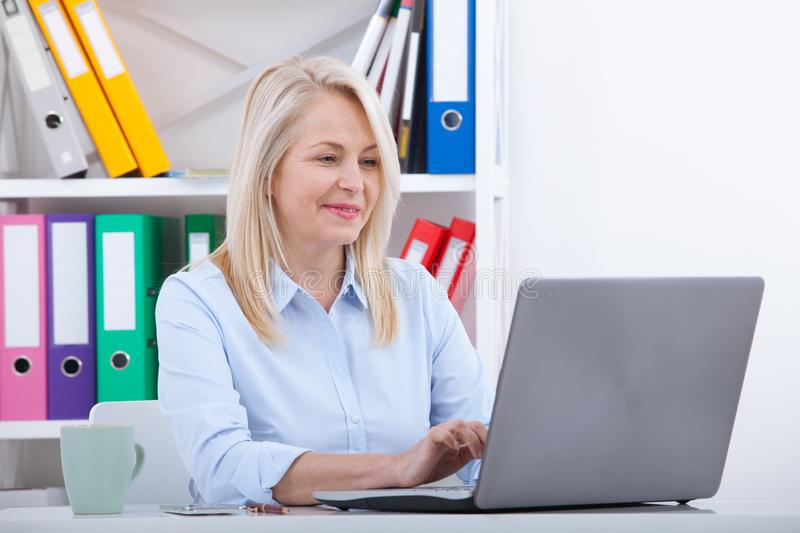 Attractive mature businesswoman working on laptop in her workplace. Business concept royalty free stock photo
