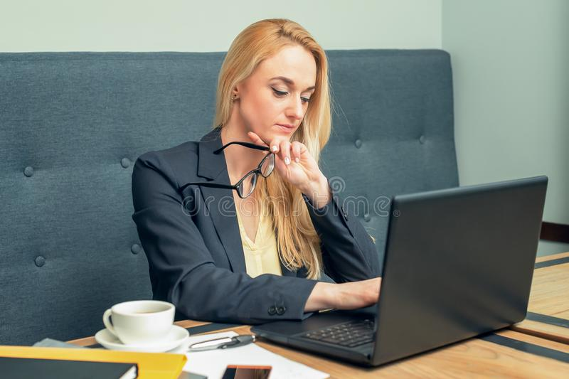 Attractive mature businesswoman is working on laptop at office royalty free stock images