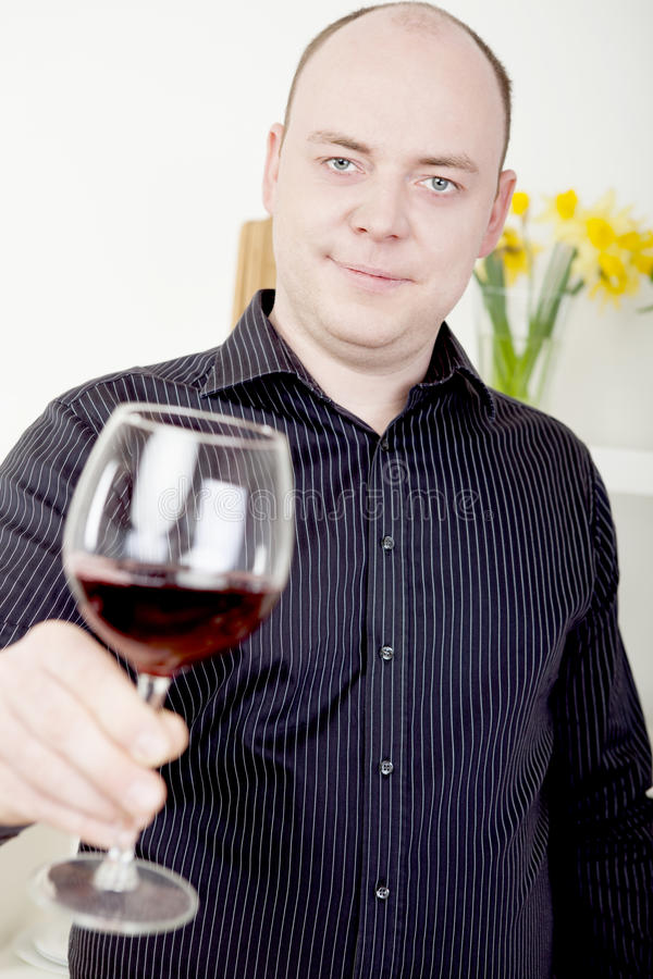 Man raising his glass in a toast. Attractive mature man raising his glass to the camera in a toast of celebration , as an acknowledgement or in a polite greeting stock image