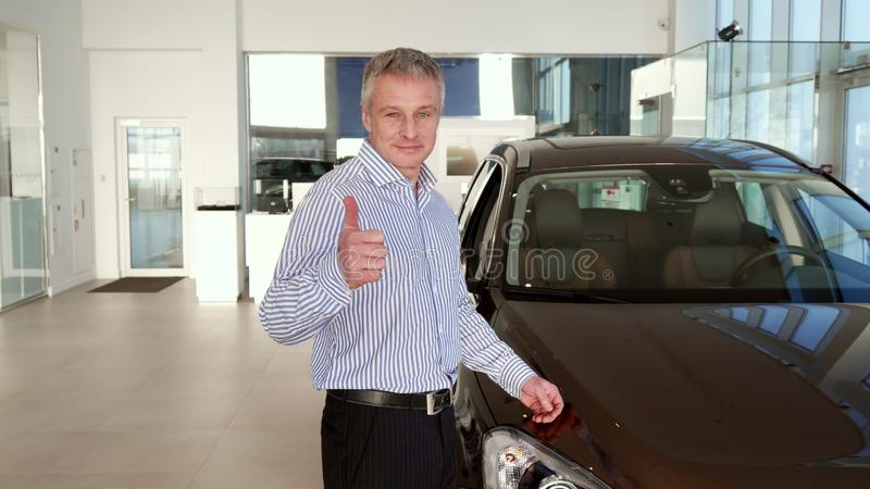 Mature man shows thumb up near the car at the dealership. Attractive mature man showing his thumb up near the car at the dealership. Middle aged gray client stock images
