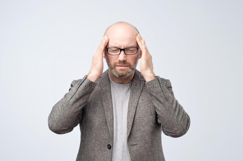 Attractive mature man touching temples with fingers, having closed eyes, suffering from headache, bad memories. Portrait of attractive mature man touching stock photos