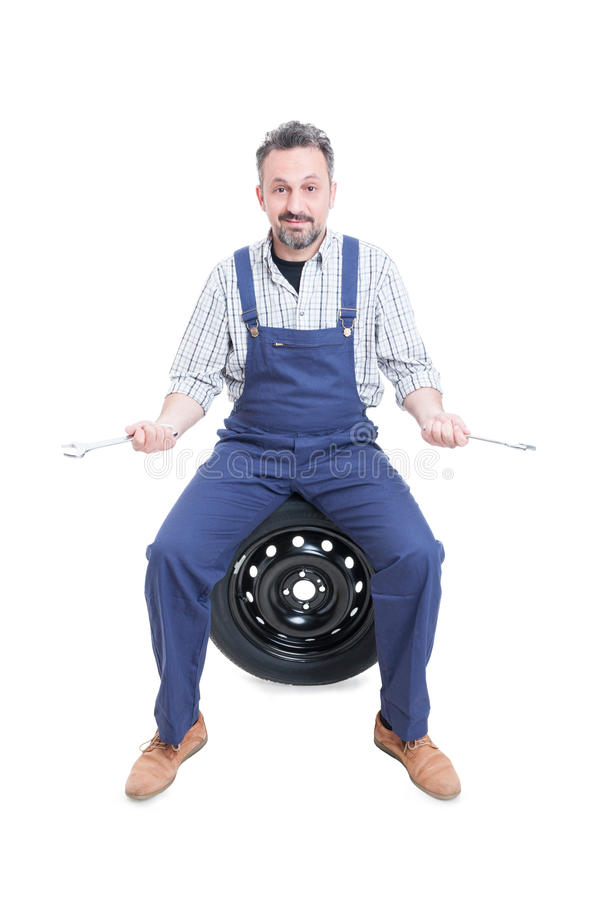 Attractive mature repairman on tire holding spanner stock photo
