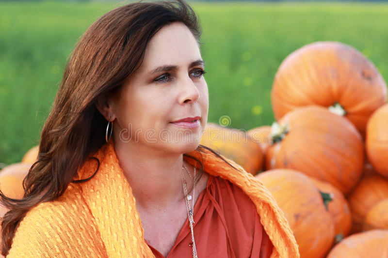 Attractive mature woman face in front of pumpkins royalty free stock photography
