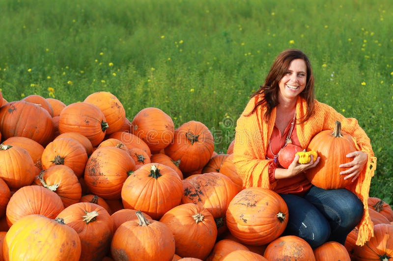 Attractive mature woman with orange pumpkins in autumn stock photography