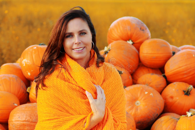Attractive mature woman with orange pumpkins in autumn royalty free stock images