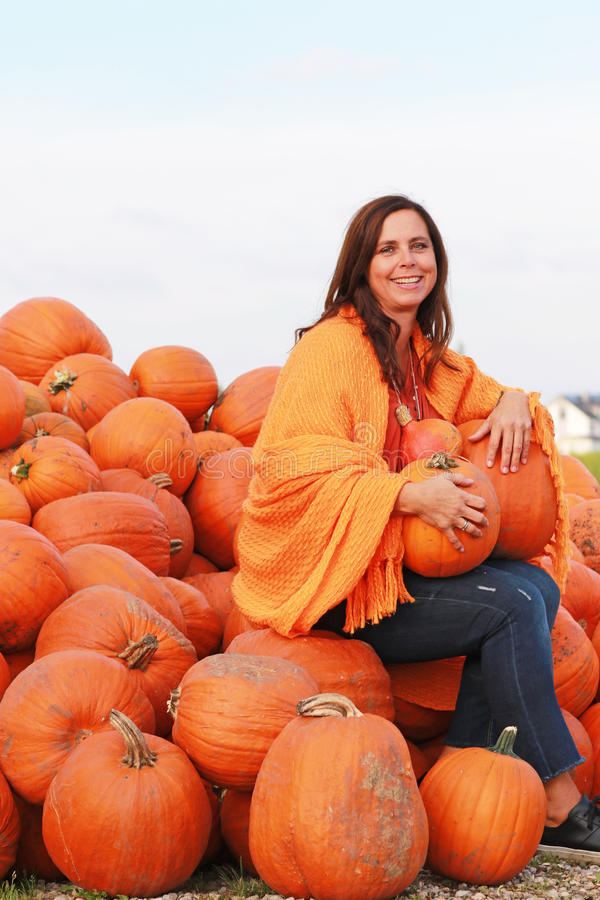 Attractive mature woman with orange pumpkins in autumn royalty free stock photos