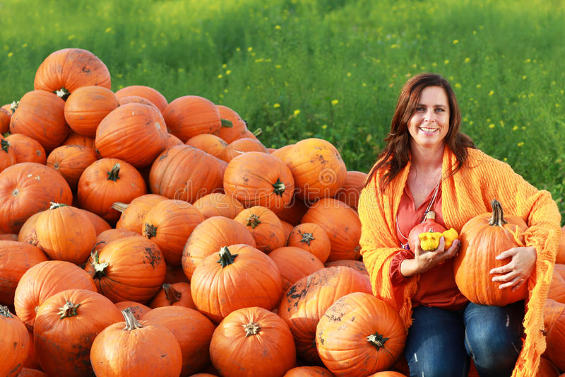Attractive mature woman with orange pumpkins in autumn royalty free stock photo