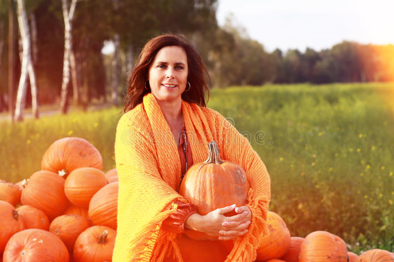 Attractive mature woman with orange pumpkins in autumn stock photo
