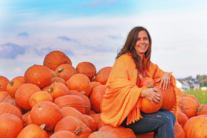 Attractive mature woman with orange pumpkins in autumn stock photos