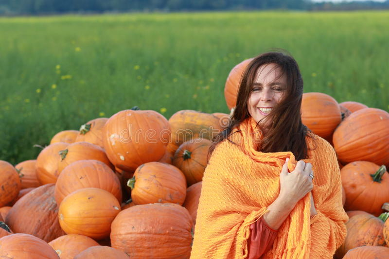 Attractive mature woman with orange pumpkins in autumn royalty free stock image